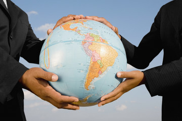 African businesspeople holding globe