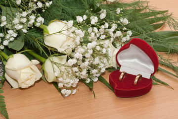 Gold rings are in box and bouquet of white roses.