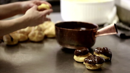 A baker is frosting cream puffs with chocolate
