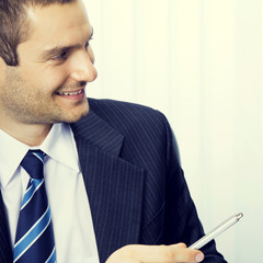 Young businessman giving pen