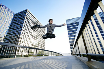 Asian businessman leaping on urban walkway