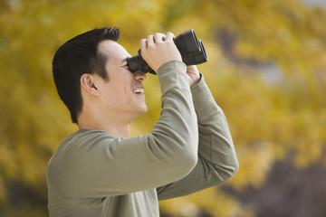 Asian man looking through binoculars