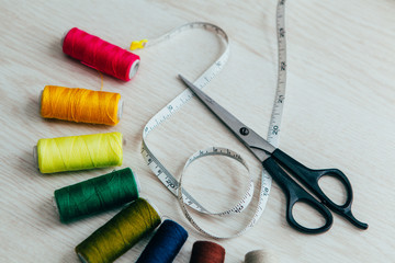 colorful sewing spools with scissors and meter tape