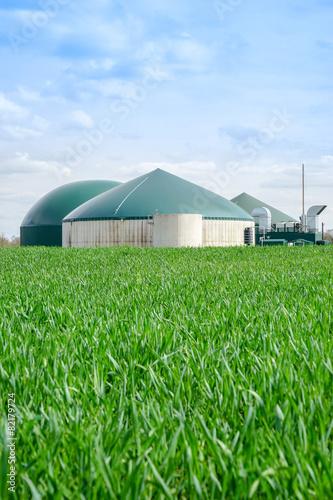 Leinwanddruck Bild Biogasanlage im Hochformat, davor grünes Getreidefeld