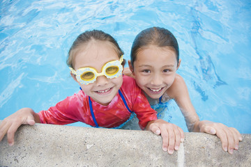 Asian sisters swimming in pool