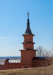 Tower with  weather vane and  monastery wall of red brick