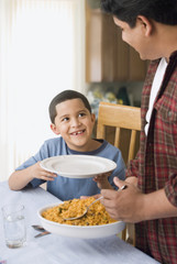 Hispanic father dishing son food at dinner table