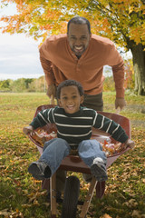 African father pushing son in wheelbarrow with autumn leaves