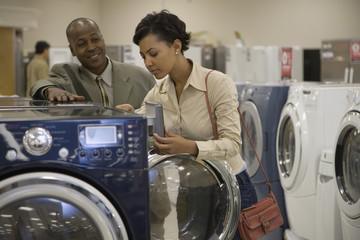 Salesman showing customer washing machine in showroom