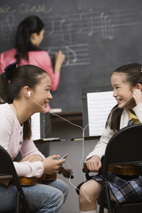 Asian girls listening to mp3 player in music class