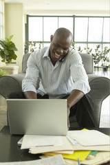 African businessman working on laptop while talking on cell phone