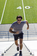Hispanic athlete running on bleacher steps