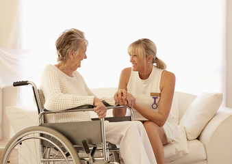 Older Caucasian woman in wheelchair talking with caregiver