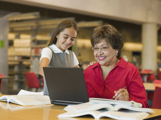 Hispanic grandmother and granddaughter looking at laptop