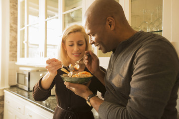 Couple sharing bowl of seafood stew in kitchen
