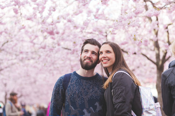 Hipster couple portrait in Stockholm with cherry blossoms