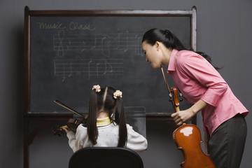 Asian female music teacher watching student play violin