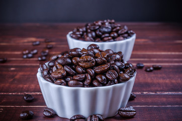 roasted coffee beans in two white bowl porcelain on wooden backg