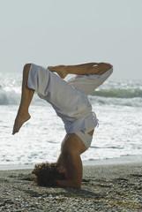 Hispanic woman doing headstand at beach