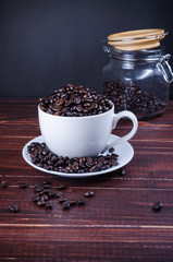 roasted coffee beans in coffee cup on wooden background