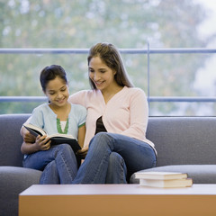 Mixed Race mother and daughter reading