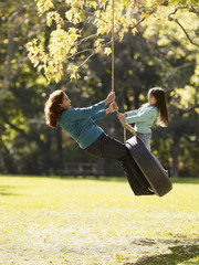 Hispanic grandmother and granddaughter swinging on tire swing