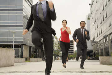 Multi-ethnic businesspeople running