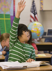 Asian boy with arm raised in classroom