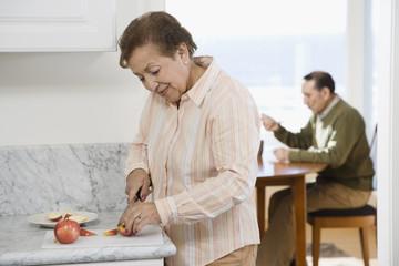 Senior Hispanic woman cutting apple