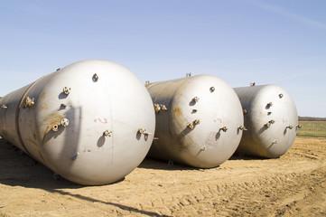 Three large metal tanks lay on the ground