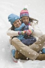 Multi-ethnic girls sledding in snow