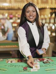 Hispanic female blackjack dealer in casino