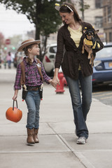 Caucasian mother and daughter walking in Halloween costumes