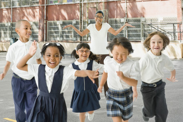 Multi-ethnic school children running from teacher outdoors