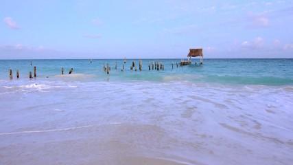 Battered dock taking surf on beautiful Caribbean beach at dusk