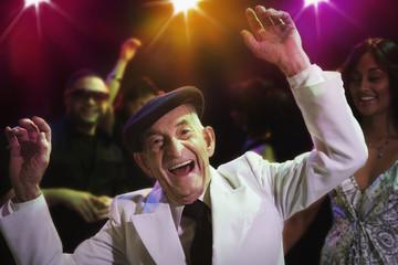 Hispanic senior man dancing in nightclub