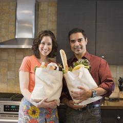 Hispanic couple holding grocery bags