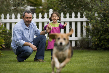 Father and daughter watching dog in backyard