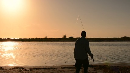 Silhouette man fishing in lagoon under golden bright morning sky