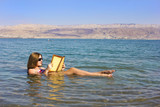 Fototapety young girl reads a book floating in the Dead Sea in Israel