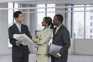 Multi-ethnic business people reviewing blueprints