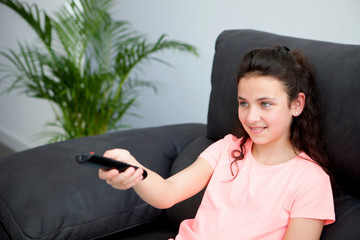 Young girl with a remote control at home
