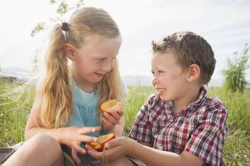 Caucasian children sharing fruit outdoors