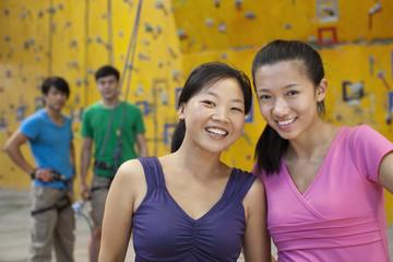 Chinese women smiling in rock climbing gym