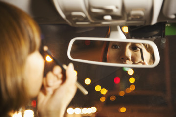 Chinese woman applying make up in car mirror