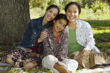 Multi-ethnic family sitting under tree