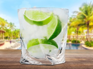 Gin. Cocktail with ice and lime slice isolated on white