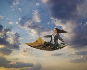Caucasian businesswoman riding magic carpet
