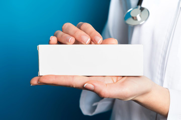 Nurse holding a medicine packet blue background