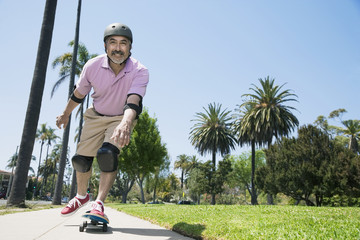 Hispanic man riding skateboard